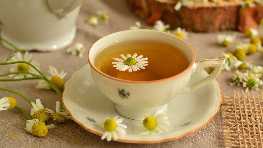 rumančekový čaj na trávenie v bielej šálke s oranžovým lemomna stole