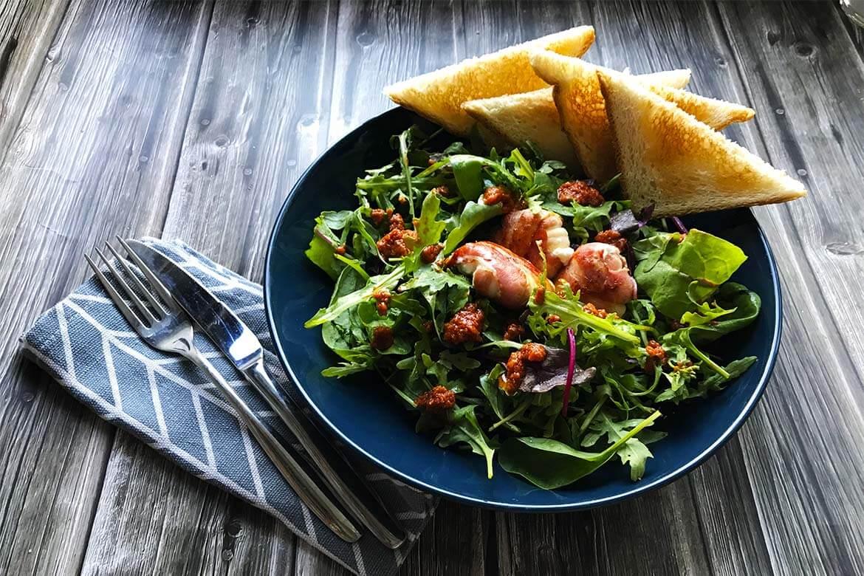 kozí syr obaleným v slaninke na listovom šaláte s pestom v tanieri s obrúskom a príborom na drevenom podklade